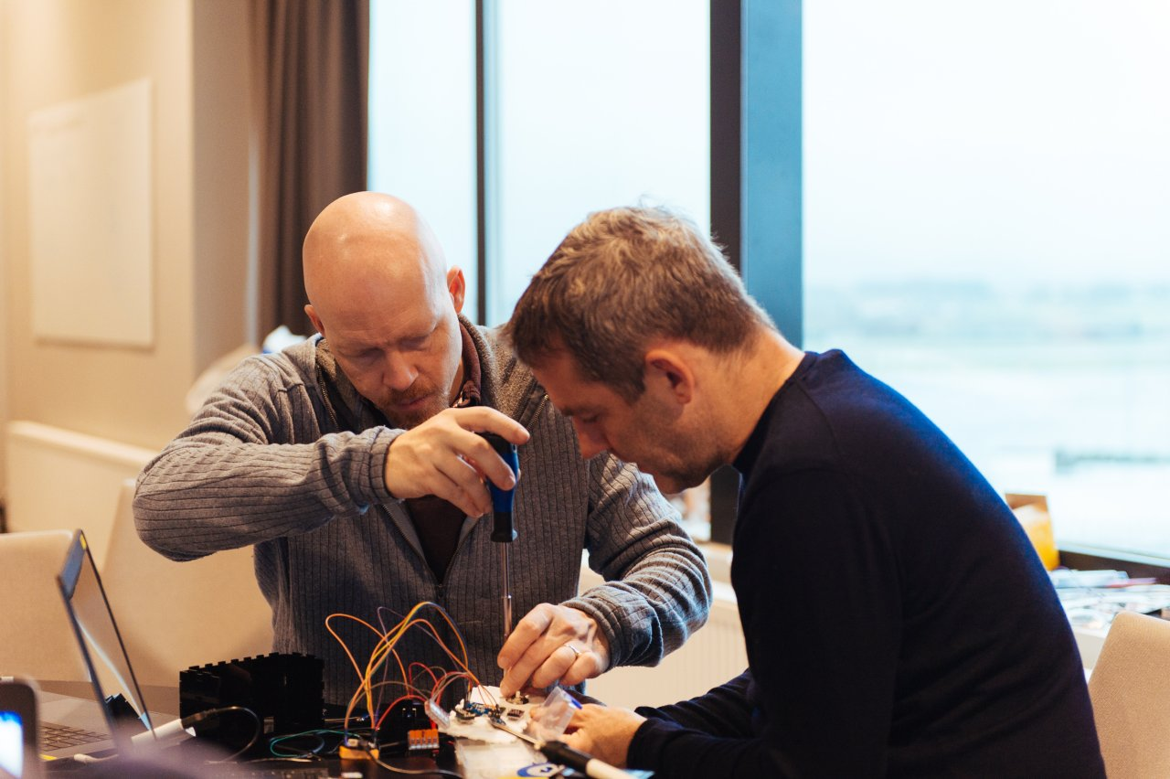 Photo of two men working on assembling computer parts