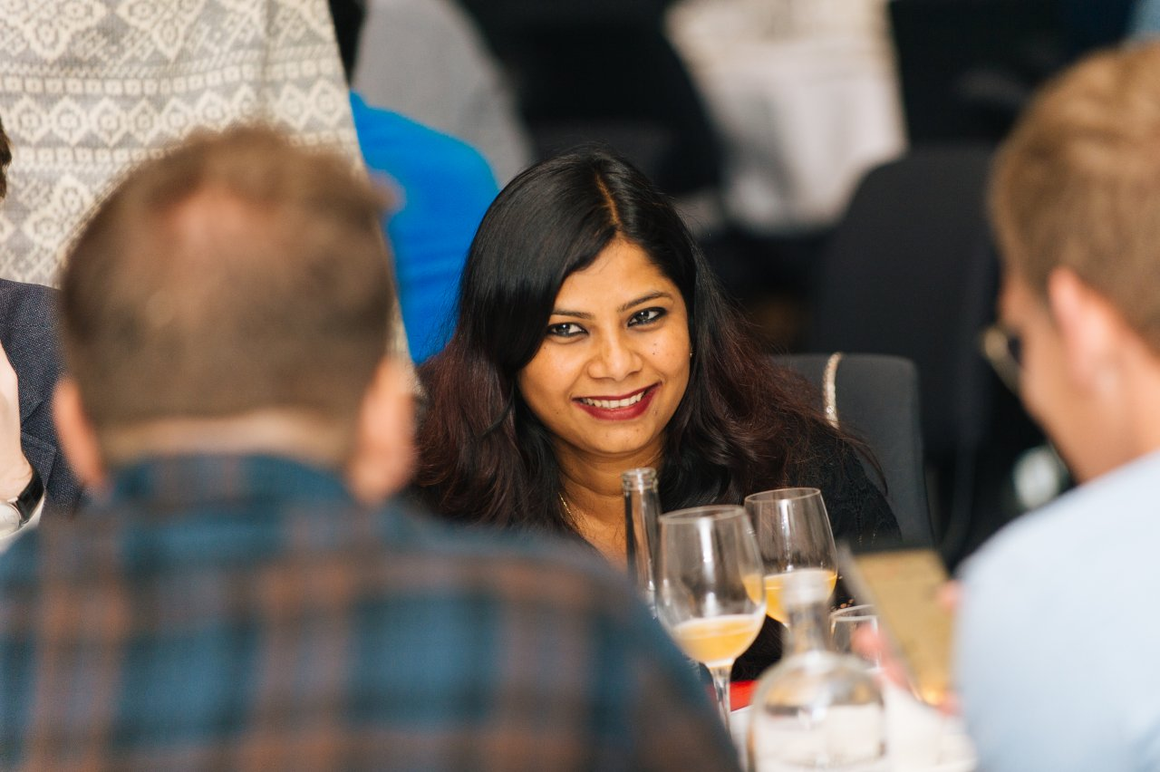 Woman smiles to colleagues during a dinner conversation