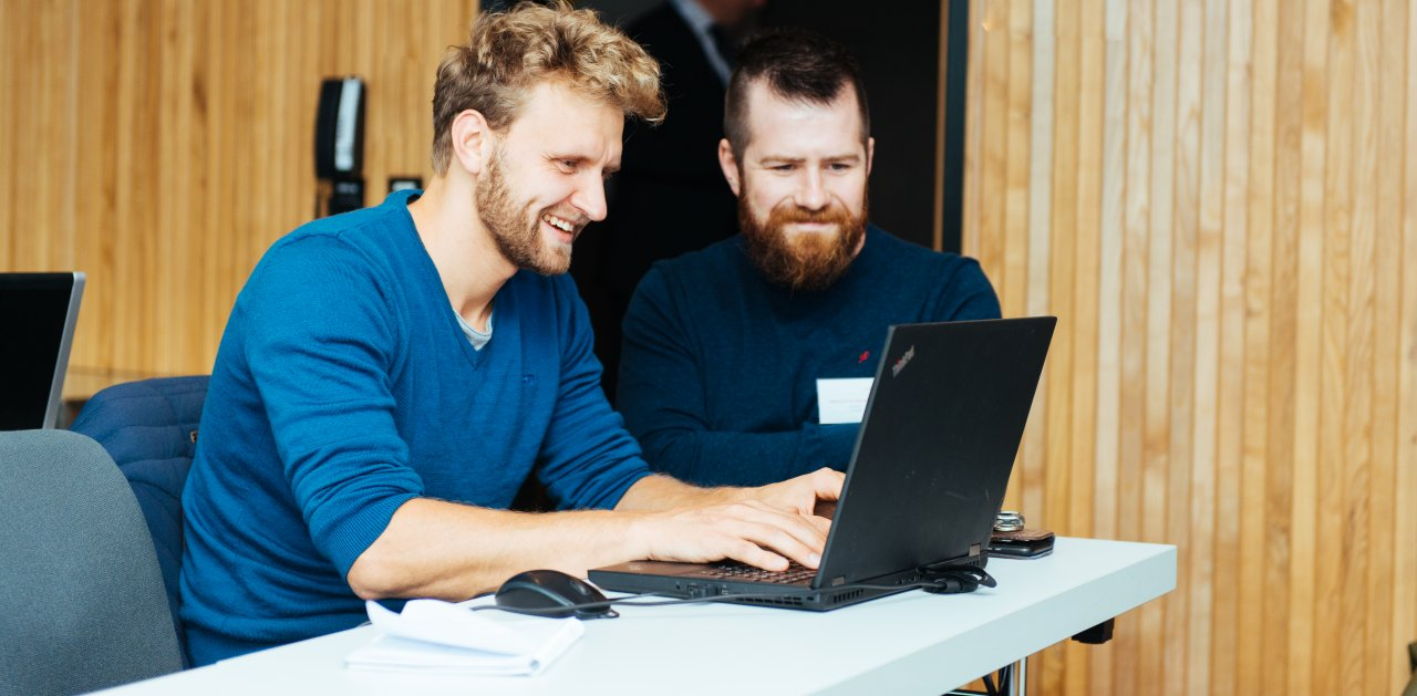 Two men looking at the same computer during Equinor Developer Conference