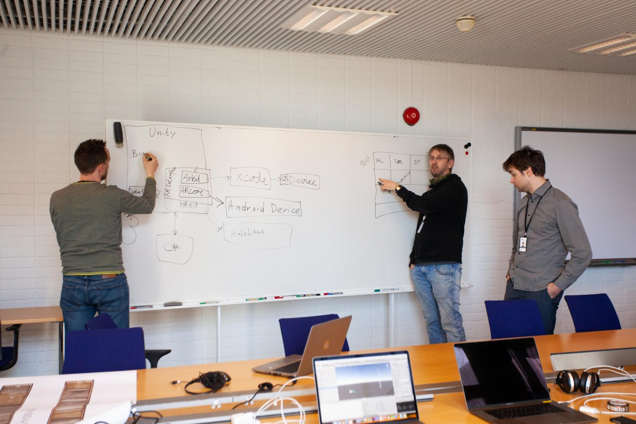 Three men writing something on a white board