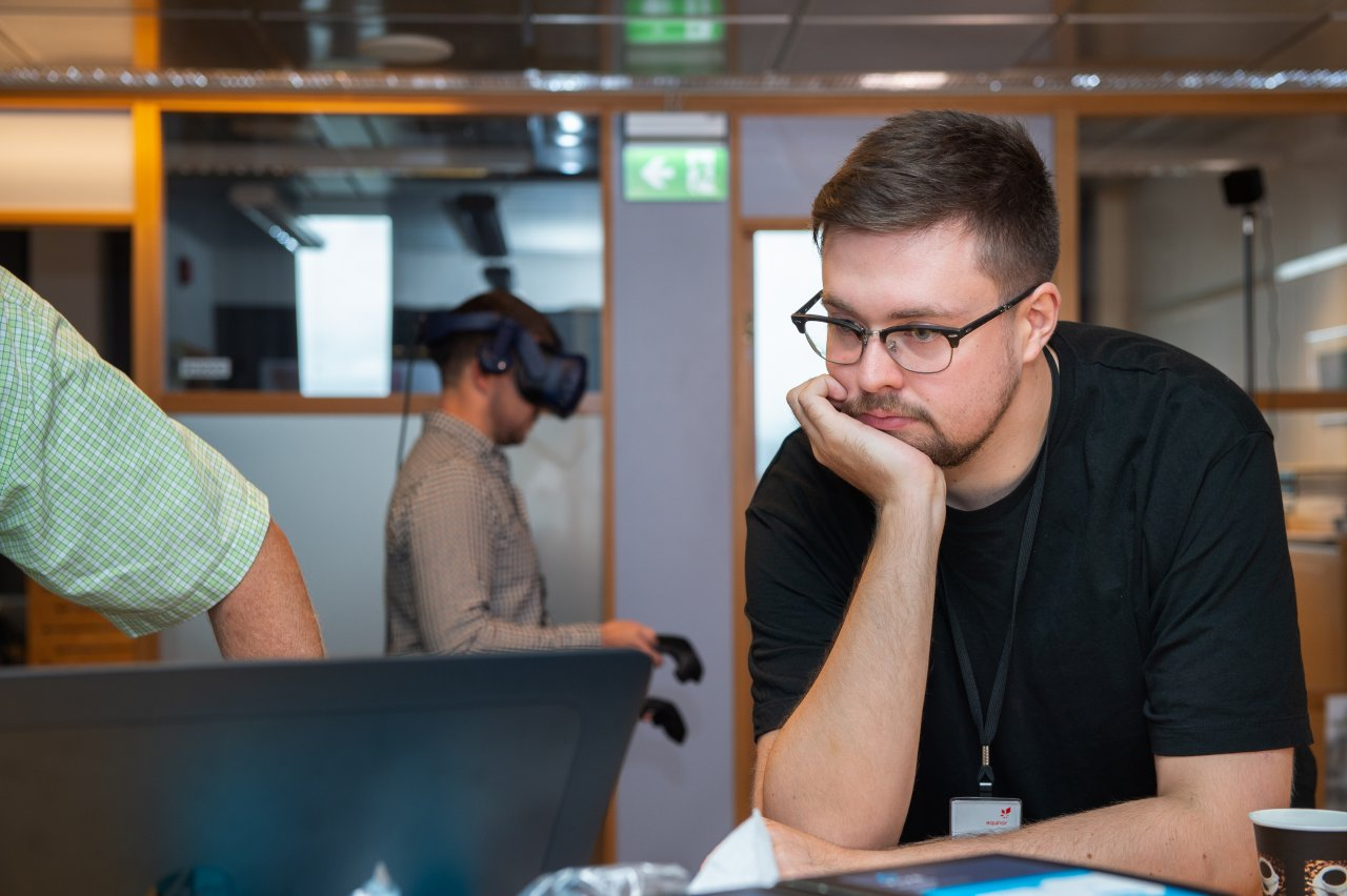 Man looking at a computer while another man wears a VR headset in the background