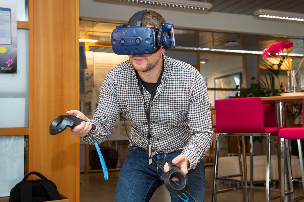 Man wearing a VR headset and kneeling in an office landscape