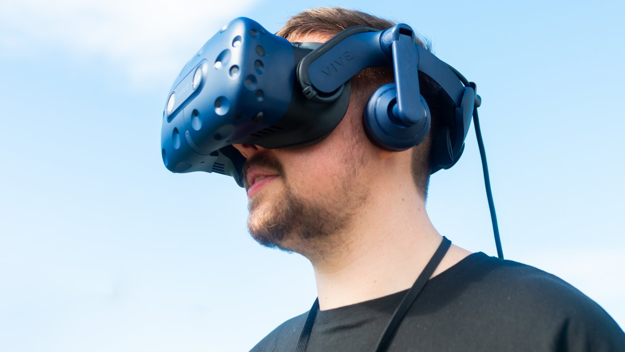 Photo of a man wearing a virtual reality headset and staring into thin air